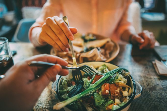woman taking food off someone else's plate in a restaurant
