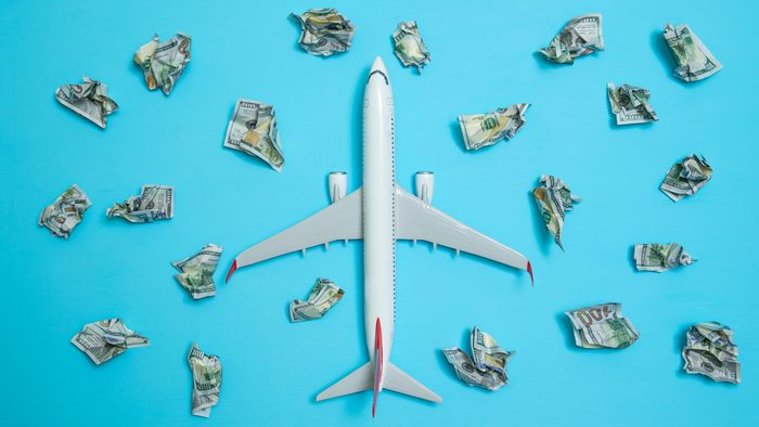 airplane on blue background surrounded by crumpled money