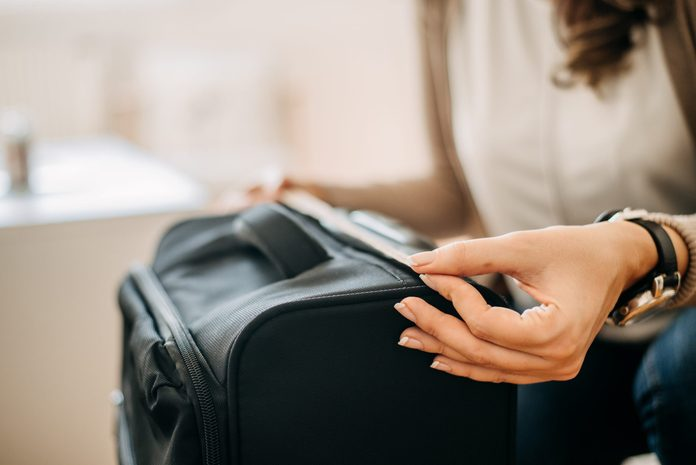 Close up of woman using measuring tape to measure carry-on luggage.