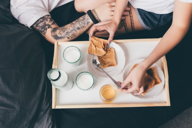 partial view of tattooed couple having breakfast with toasts and milk together in bed