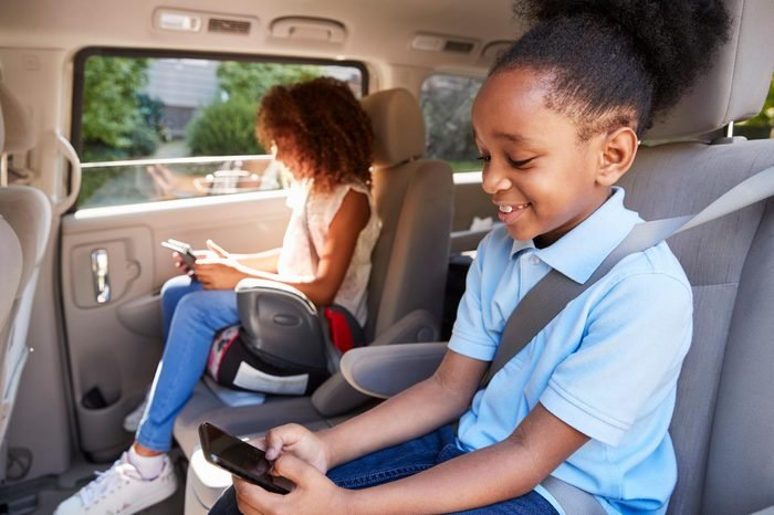 children in booster seats using devices in the car