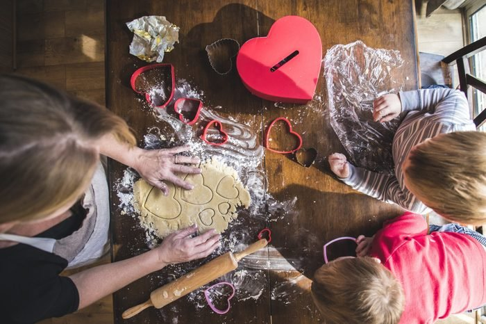 Valentines Day Baking heart shaped sugar cookies with her children