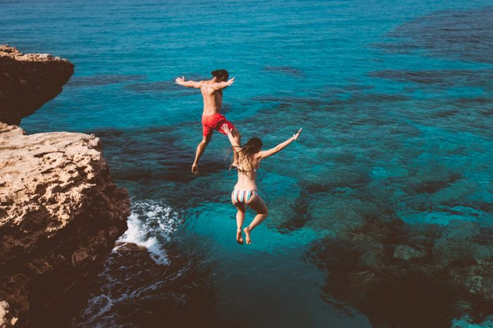 couple jumping off a cliff into the ocean on vacation