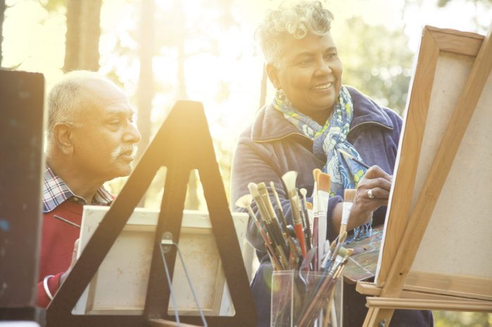 Mixed race, active senior adult couple enjoys art hobby together outdoors in public park or forest area. Or instructor and student taking art lessons. African and Indian ethnicities.