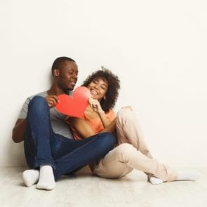 Young happy african-american couple in love holding red paper heart