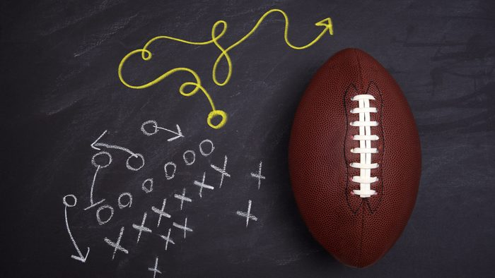 football and chalkboard with play route. x's and o's.