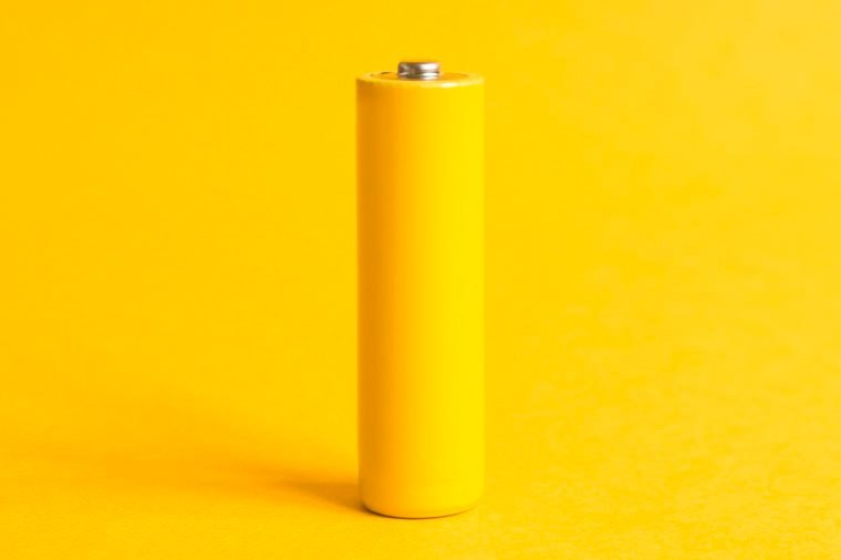 Single yellow battery on a yellow pastel background