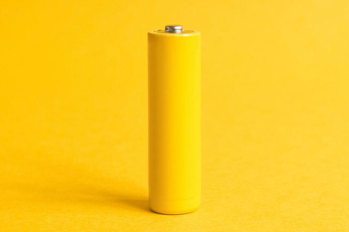 Single yellow battery on a yellow pastel background