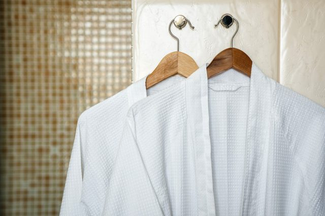 Two white rag bathrobes towels on wooden hangers