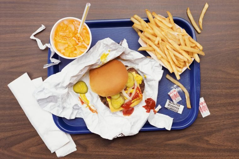 overhead view of fast food tray with burger, fries, and a drink