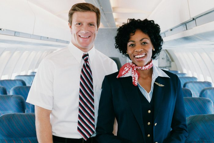 male and female flight attendants stand in the aisle of an empty airplane