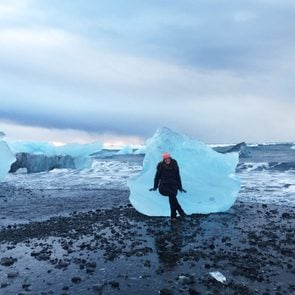 Madeline Wahl sitting on an iceberg on a beach in iceland