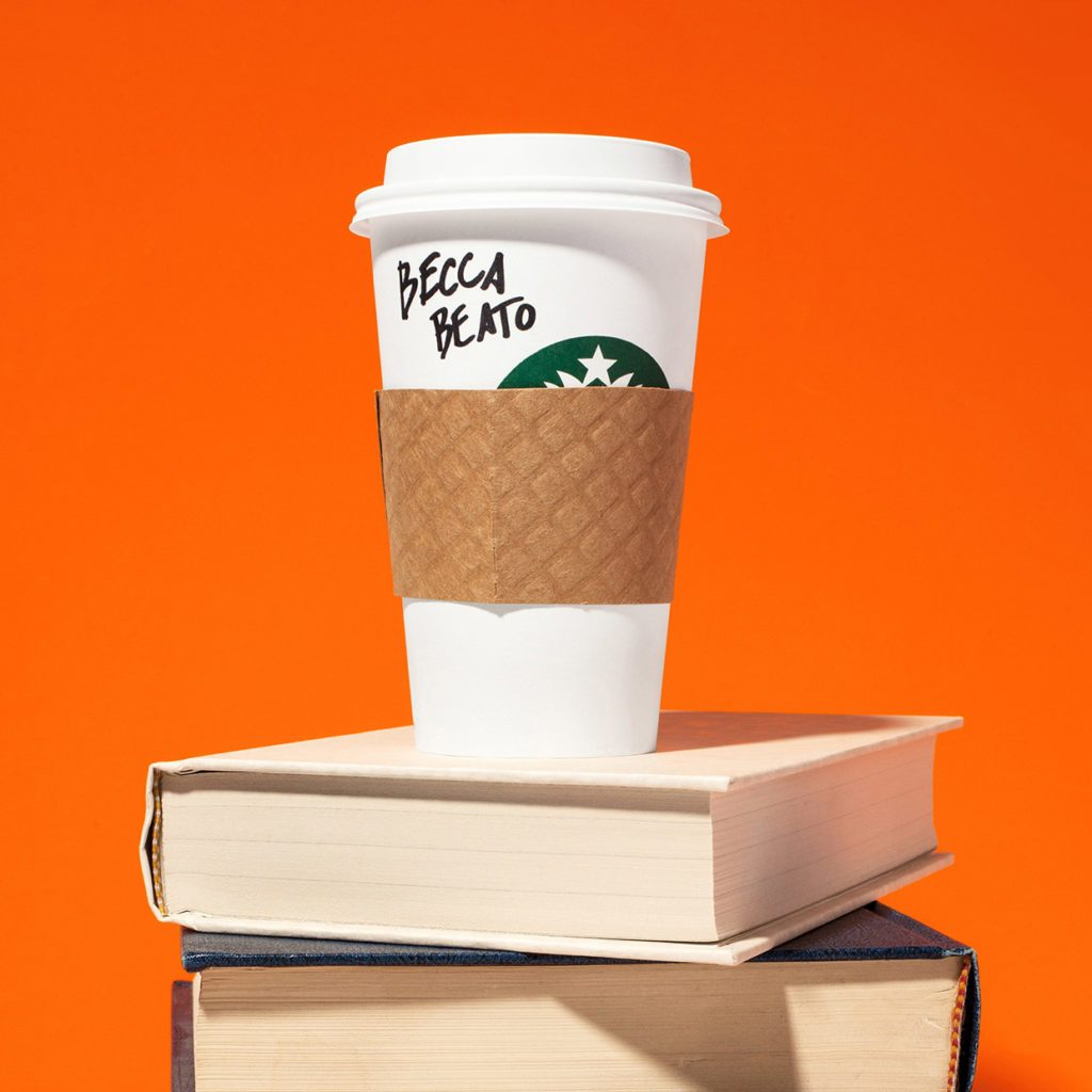 coffee cup on a stack of books. orange background.