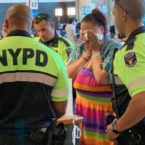 police officers stand around a distraught woman at the check out area in a grocery store
