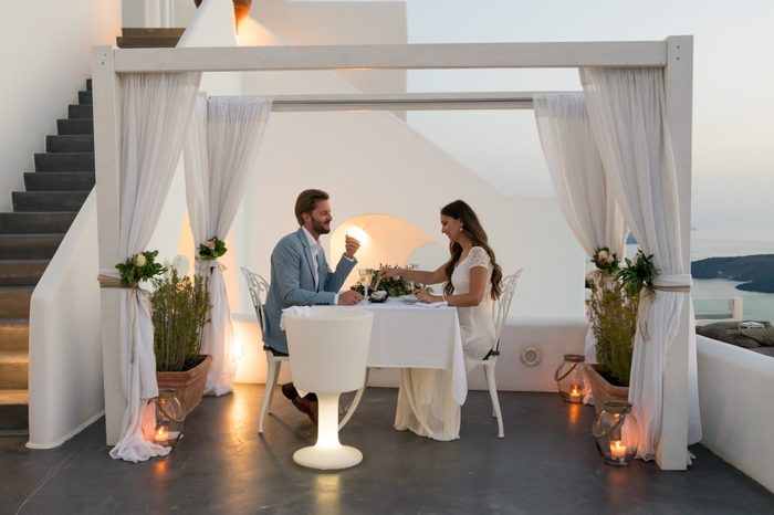 couple having candlelight dinner on romantic terrace with seaview honeymoon, vacation