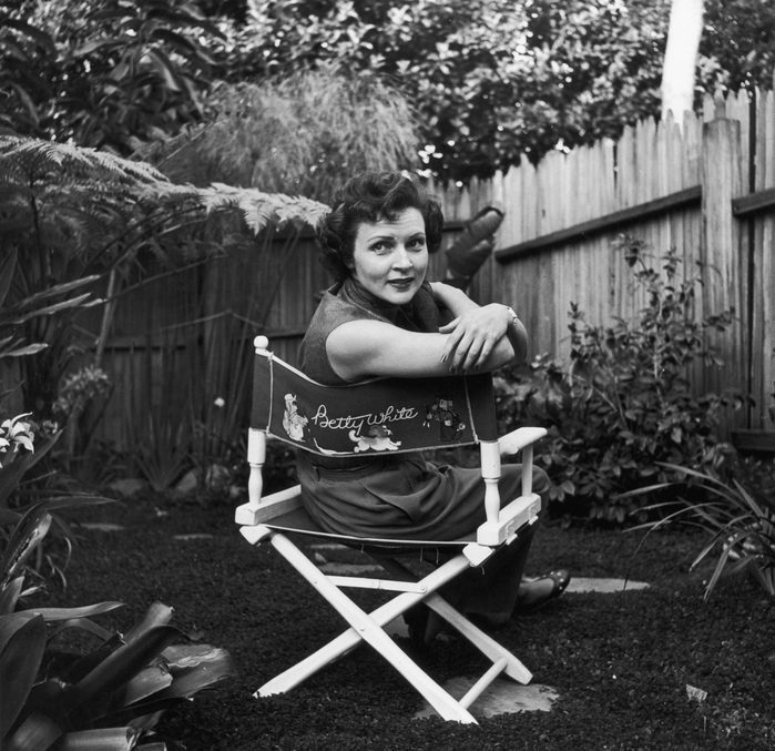 circa 1956: American actor Betty White sits in a canvas chair with her name written on the back, looking over her shoulder in a backyard garden.