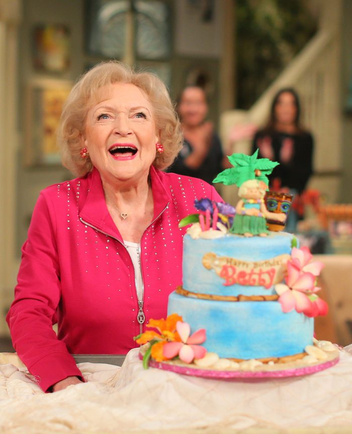 """Actress Betty White poses next to her cake at the celebration of her 93rd birthday on the set of """"Hot in Cleveland"""" January 16, 2015"""