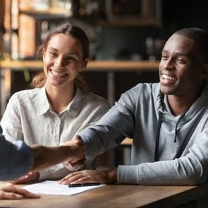 Happy young interracial couple shake hand of bank manager broker buy insurance services take mortgage loan, mixed ethnicity customers handshake agent make agreement financial business deal at meeting