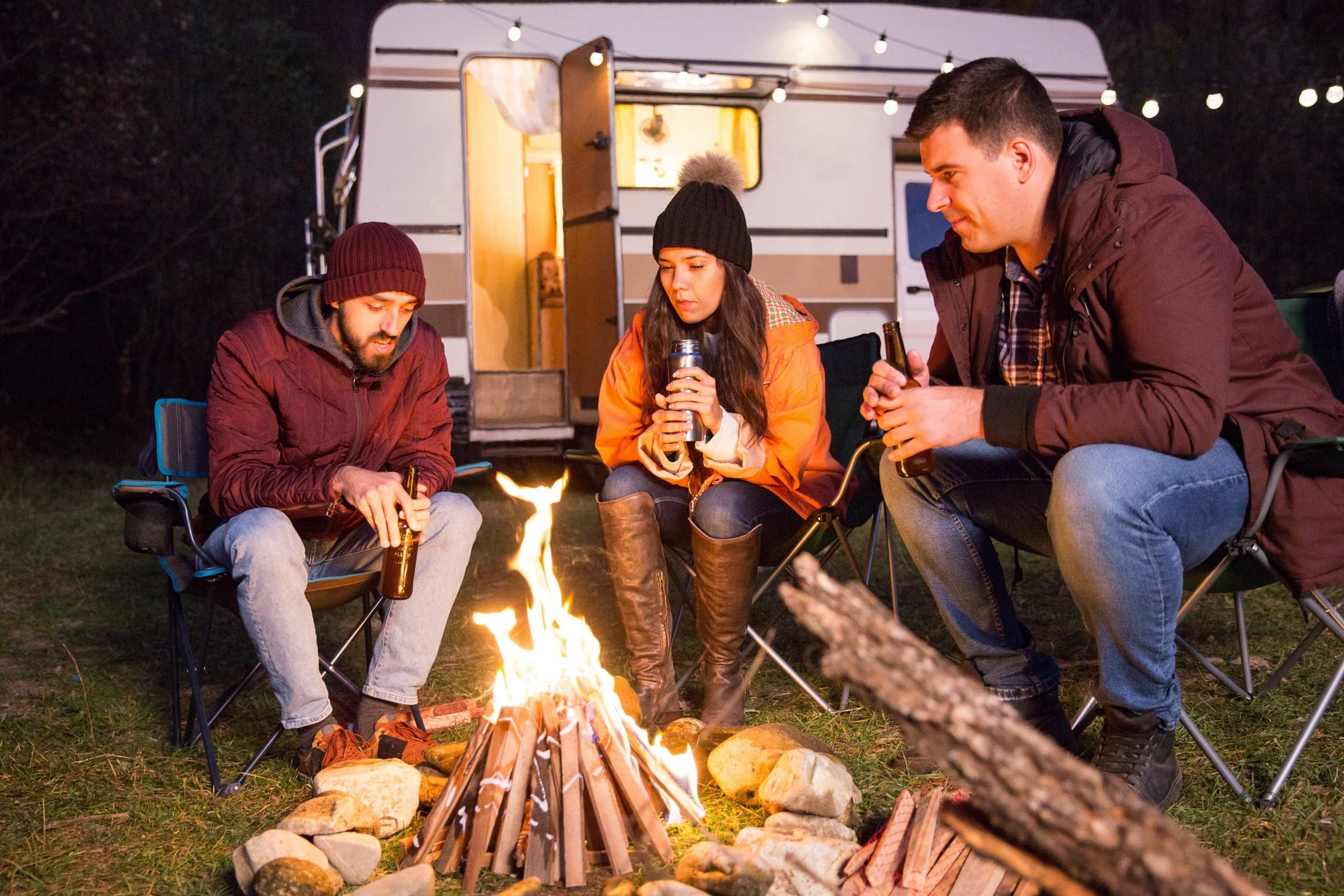 Close friends sitting together on camping chairs around camp fire in the mountains. Retro camper van.