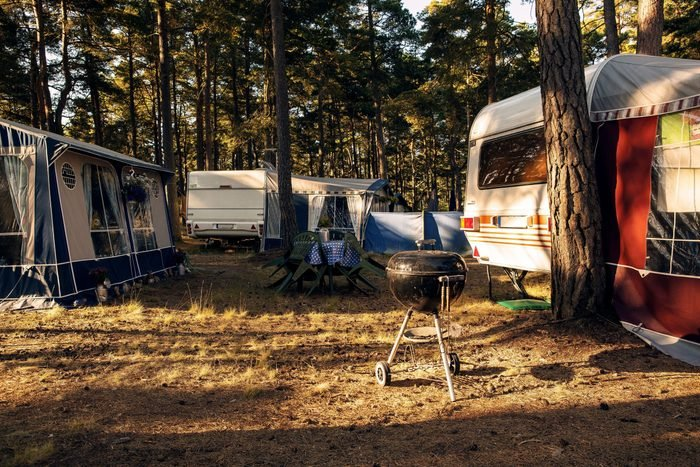 trailers on a sleeping campground in the early morning, cold grill in the foreground