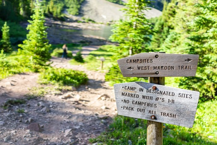 Maroon Bells trail direction sign for campground in Aspen, Colorado in July 2019 summer on path road closeup view