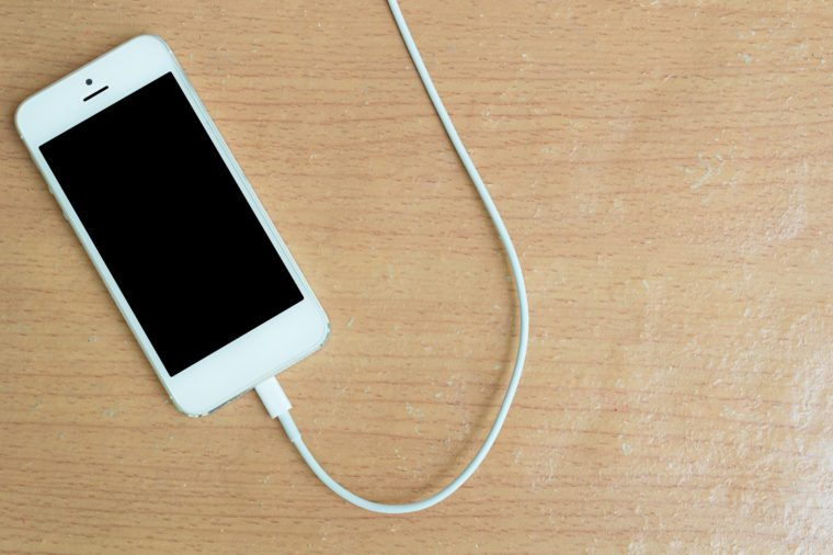 USB cable with smartphone on wood table