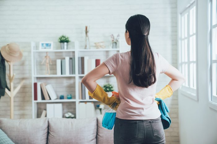 back view of asian housekeeper looking at the clean living room after she tidied up. young wife finished house chores putting hands in waist watching the bookshelf beside the sunlight window.