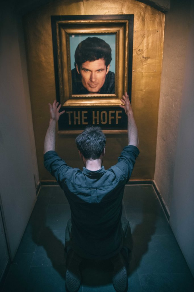 a man on his knees worships a framed image of david hasselhoff