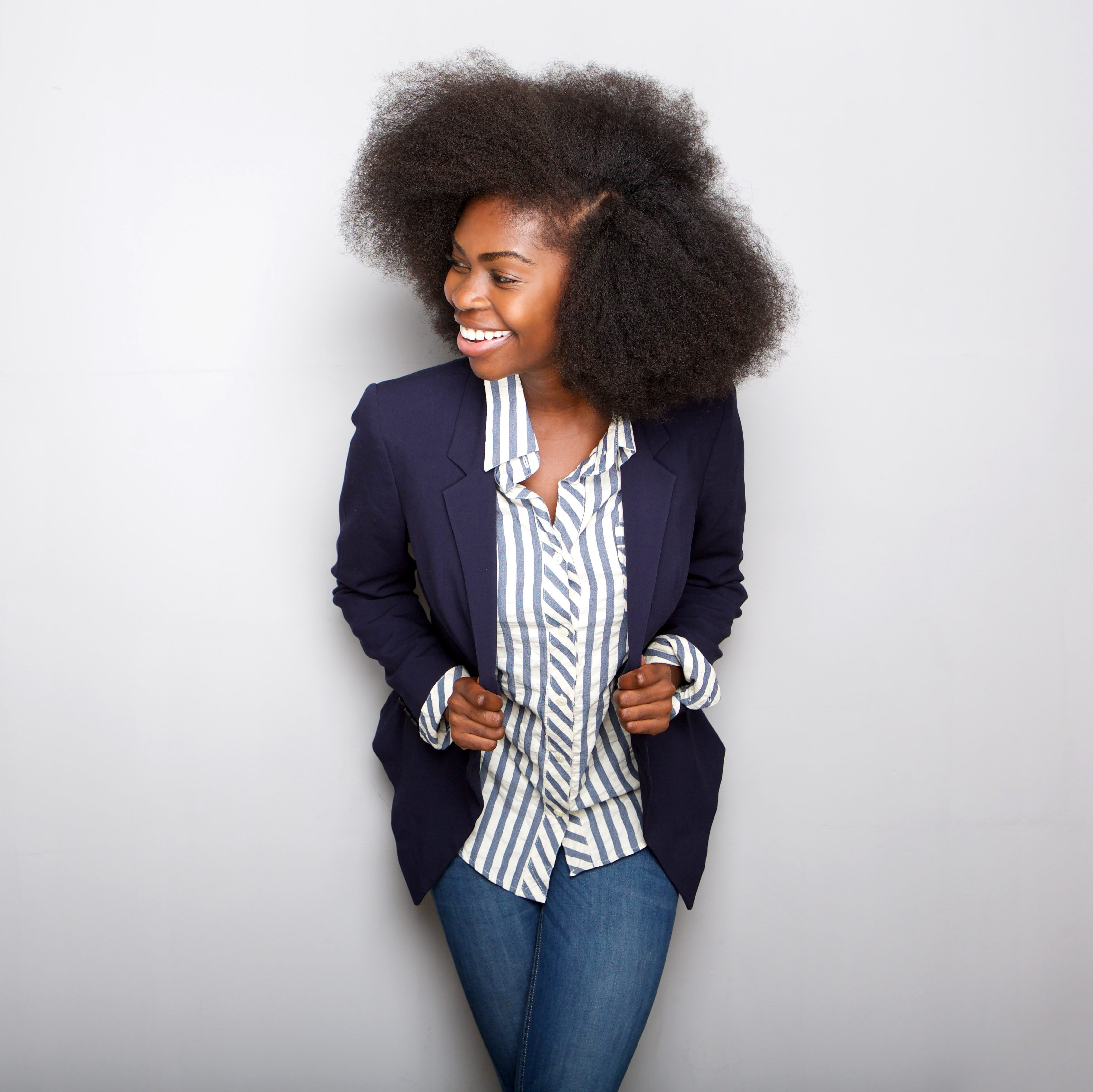 Portrait of attractive young black woman smiling with blazer against gray background