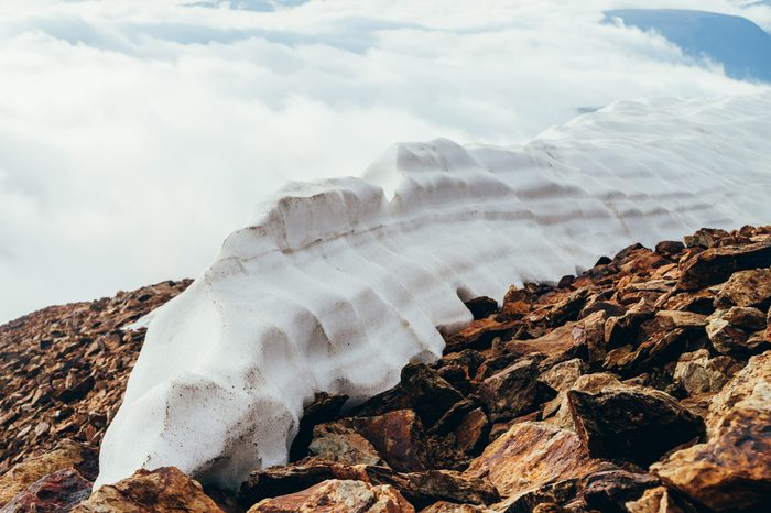 Large snowy dome on mountain top close-up. Firn on stony mountain peak on background of clouds. Snow on mountain on high altitude. Atmospheric minimalist alpine landscape. Wonderful highland scenery.