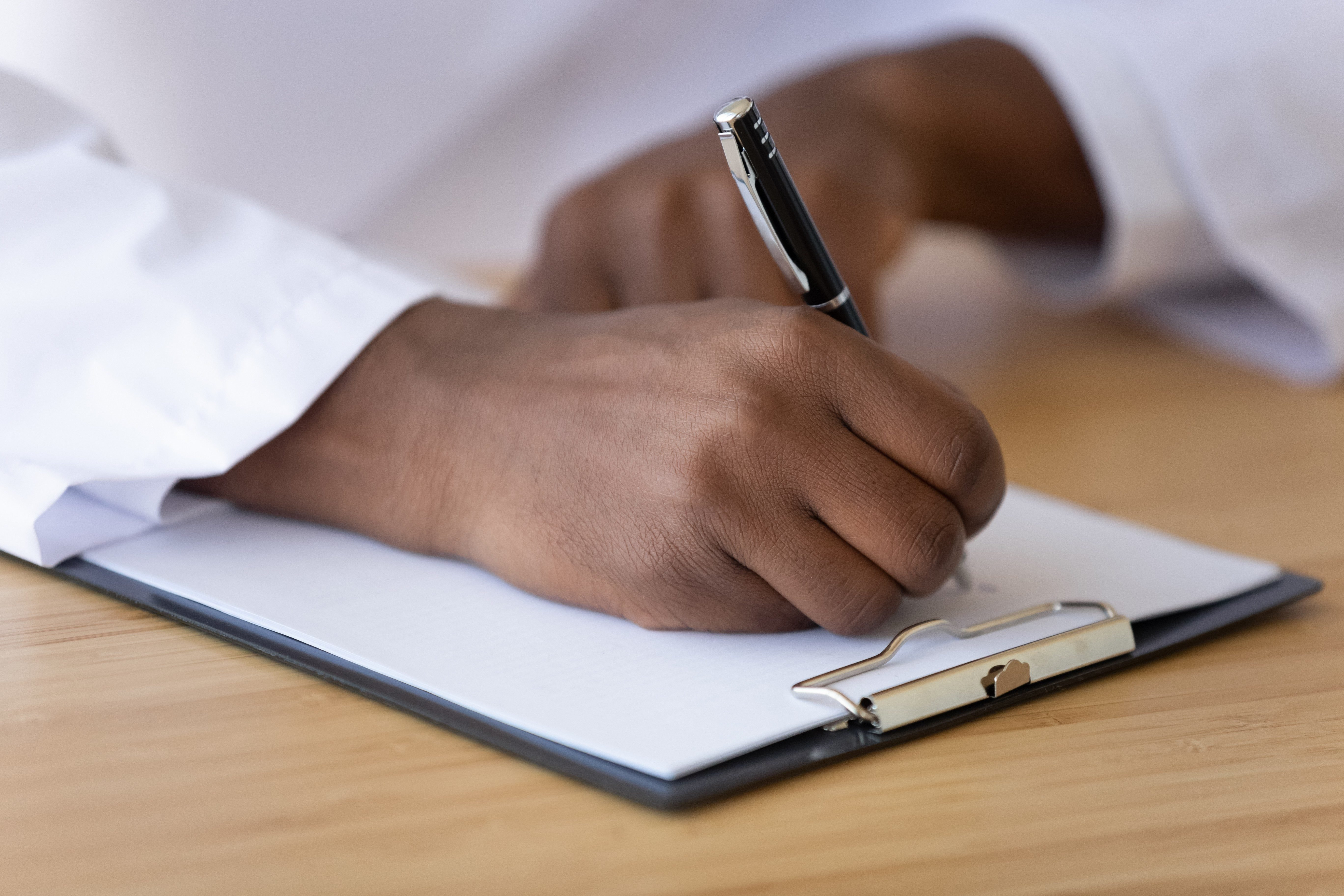 African American doctor writing on paper close up, filling patient form, document, medical history or anamnesis, sitting at desk, disease prevention, healthcare, health insurance contract
