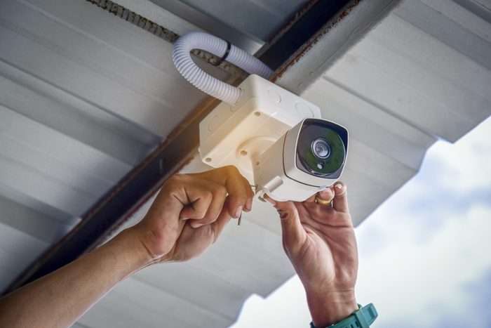 Technician installing CCTV camera by screwed for home security system and car park installed white plastic boxes for safe from water and rain