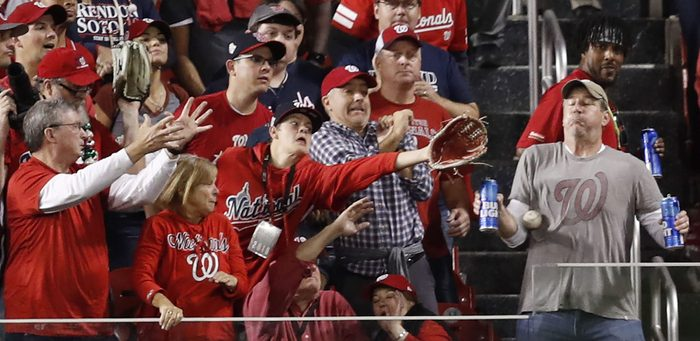 a baseball hits a fan holding beer in the stands at nationals park in washington dc during game five of the world series