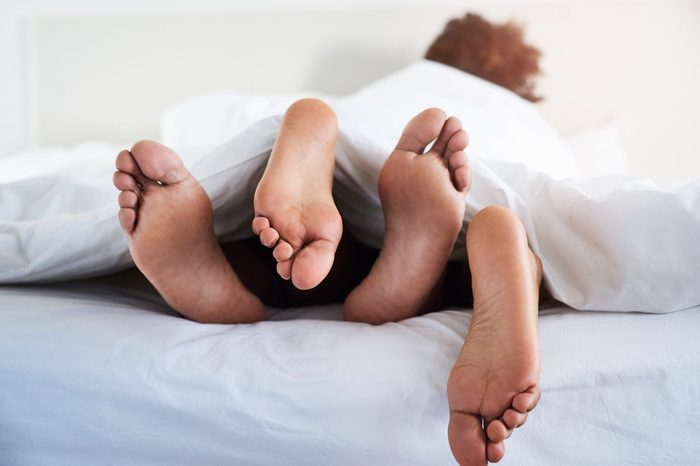 Shot of a couple's feet poking out from under the sheets