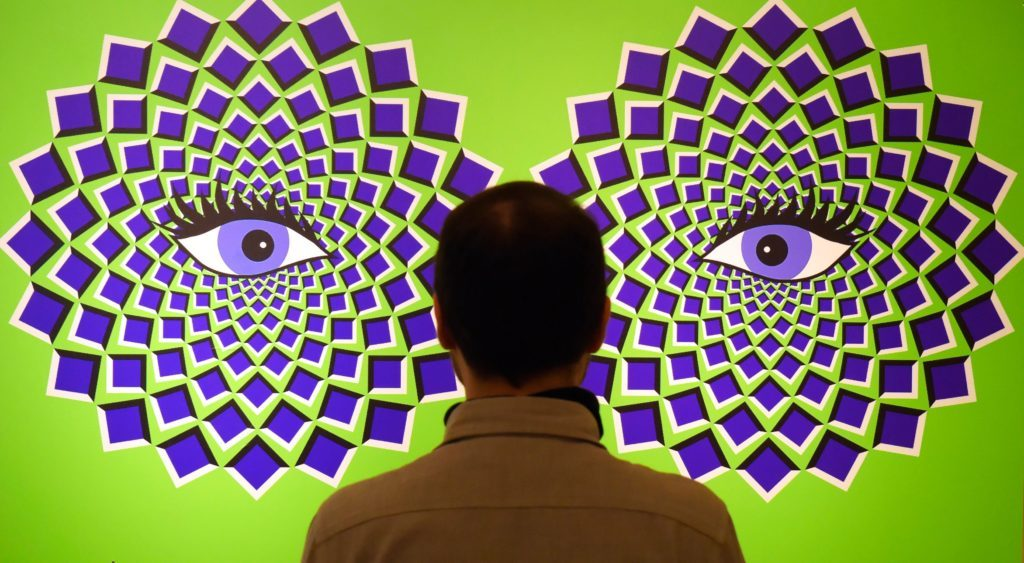 A man stands in front of a optical illusions picture