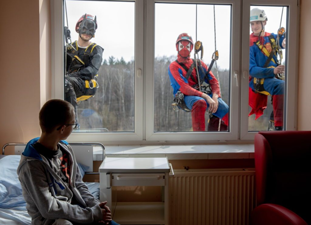 a boy looks outside his hospital window at the window washers dressed as superheros