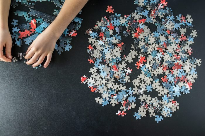 Hands of a child doing a puzzle at table