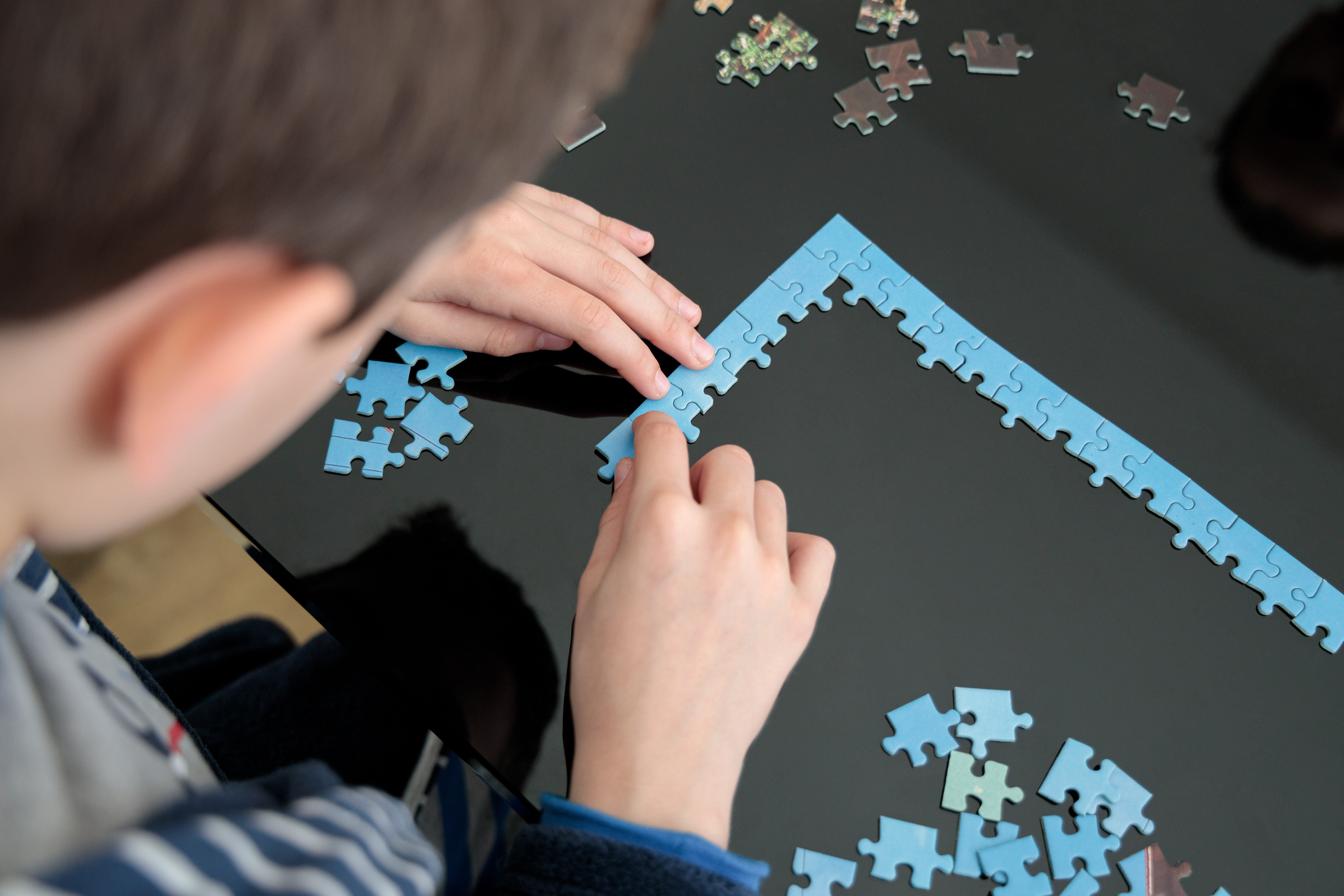 Hands, head and jigsaw puzzle pieces on a table