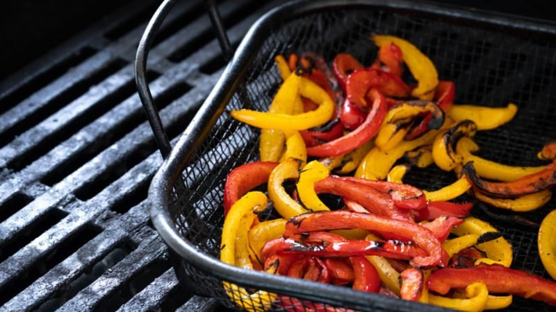 Charred yellow and red bell peppers, in a barbecue grill basket