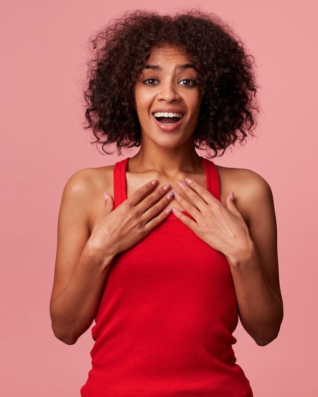 Studio photo of young happy African American male wearing a red t-shirt, with curly dark hair. Smiling, putting palms to chest, because someone made a nice compliment. Isolated over pink background.