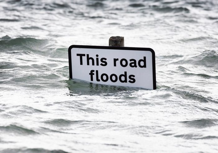 A sign says 'This road floods' as high tide covers roads in the village of Bosham in West Sussex.