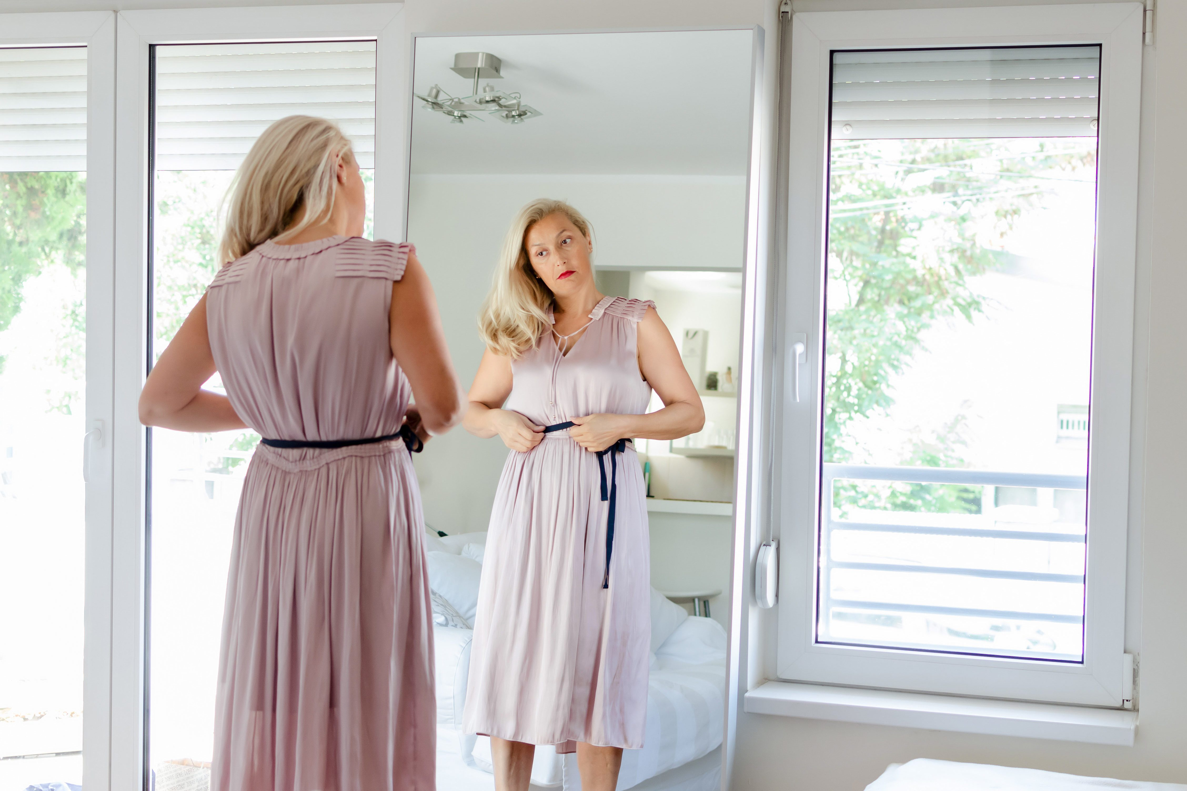 Senior woman in front of mirror getting ready, wearing a pink dress.
