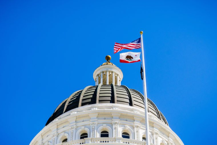 The US and the California state flag waving in the wind in front of the dome of the California State Capitol