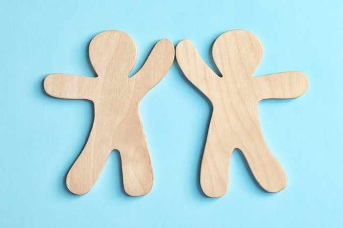 Wooden people giving high five on color background. Unity concept