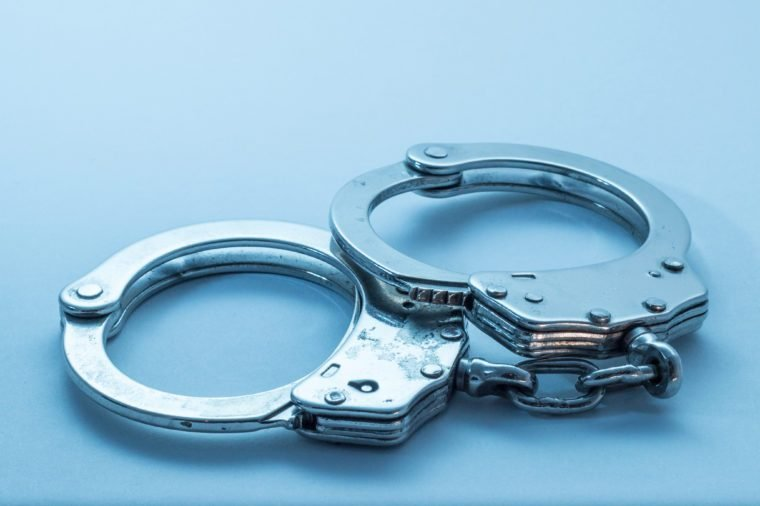 Handcuffs with signs of usage on blue background
