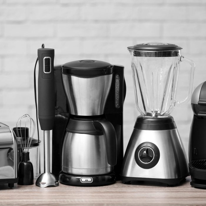 Kitchen appliances on table against brick wall background. Interior element; Shutterstock ID 1106037485