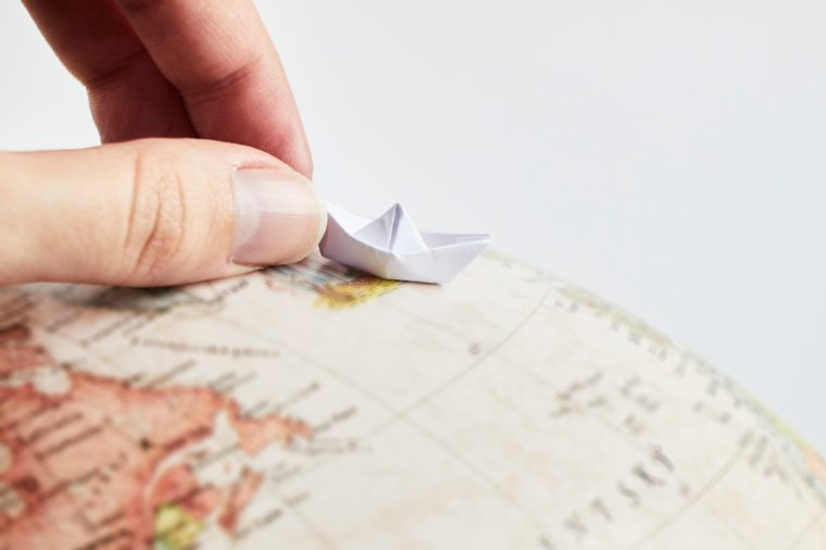 Closeup of a hand holding a little paper boat on a globe on white background.