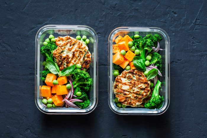 Healthy balanced lunch box. Grilled chicken zucchini burgers with broccoli, pumpkin, green pea salad on a dark background, top view. Office food lunch healthy lifestyle concept