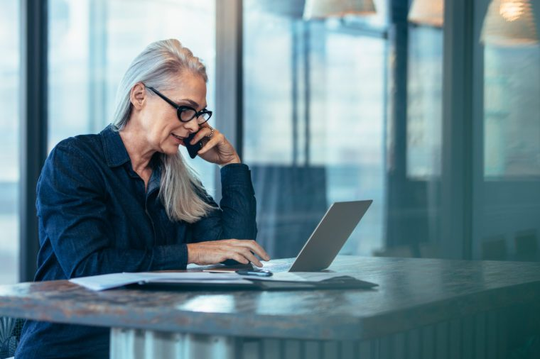 Senior business woman talking on cell phone while working on laptop in office. Mature female using laptop and talking on mobile phone.