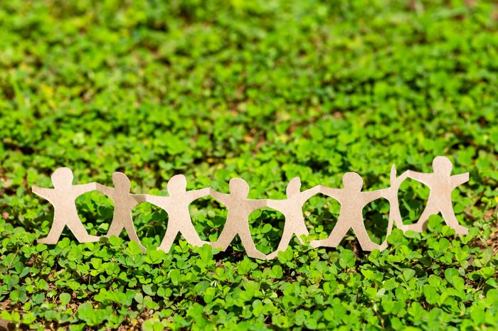 Human chain paper on green creeper plant, CSR (coporate social responsibility) or teamwork concept